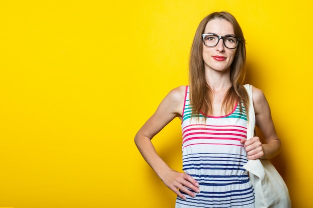 Friendly young girl wearing glasses holds a linen bag on her shoulder on a yellow background.
