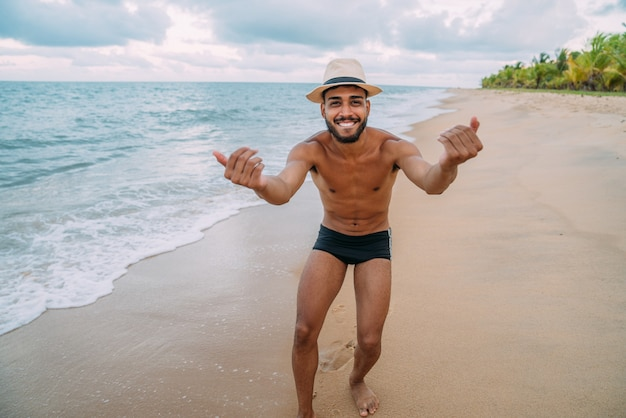 ブラジルに来るように誘うフレンドリーな若いラテンアメリカ人男性、自信を持って笑顔で手振りをし、前向きでフレンドリー