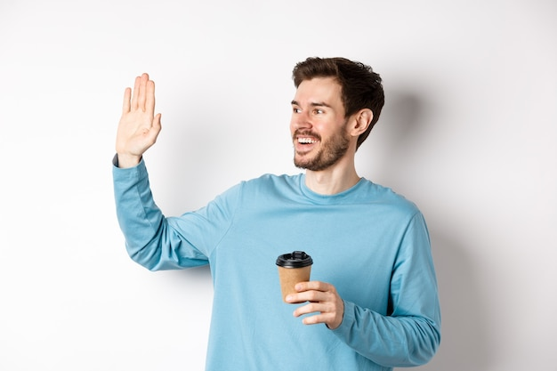 Friendly young man drinking coffee from takeaway cup and saying hello, waving hand left and smiling, standing over white background.