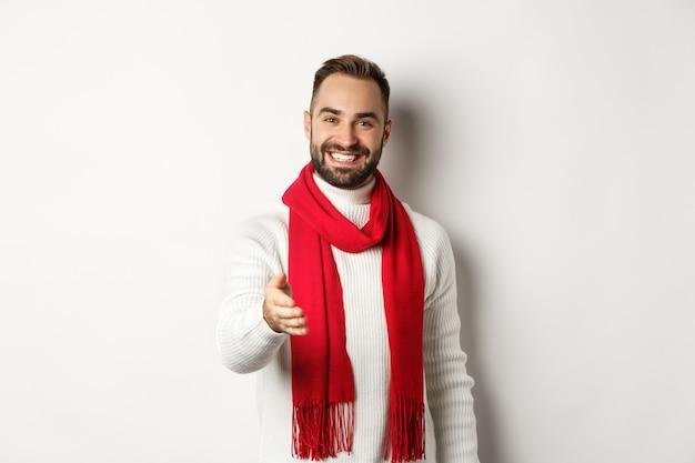 Дружелюбный молодой человек приветствует человека рукопожатием, улыбается и желает счастливого рождества, в красном шарфе и зимнем свитере, на белом фоне.