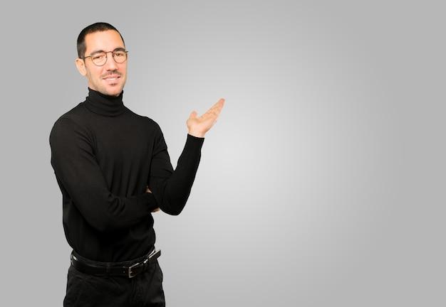Дружелюбный молодой человек делает приветственный жест