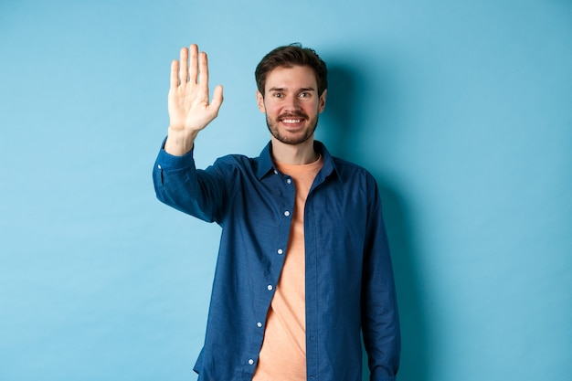 Friendly young man smiling and raising hand up for high five, waiving to greet or say hello, standing on blue background.