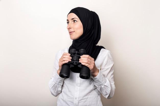 白いシャツとヒジャーブのフレンドリーな若いイスラム教徒の女性は笑顔で双眼鏡を保持します