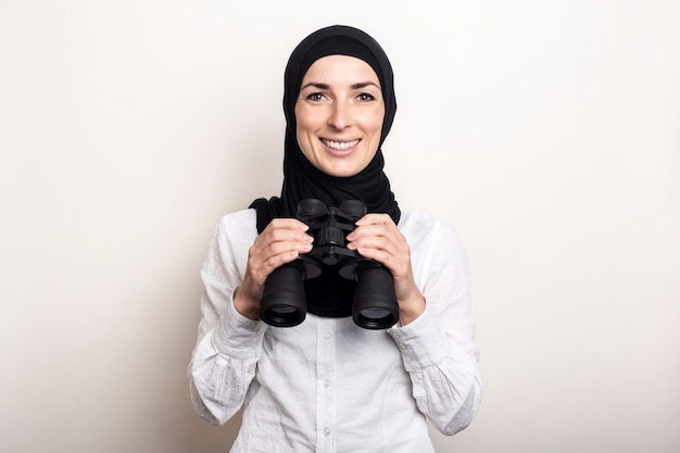 Friendly young muslim woman in white shirt and hijab holds binoculars with a smile