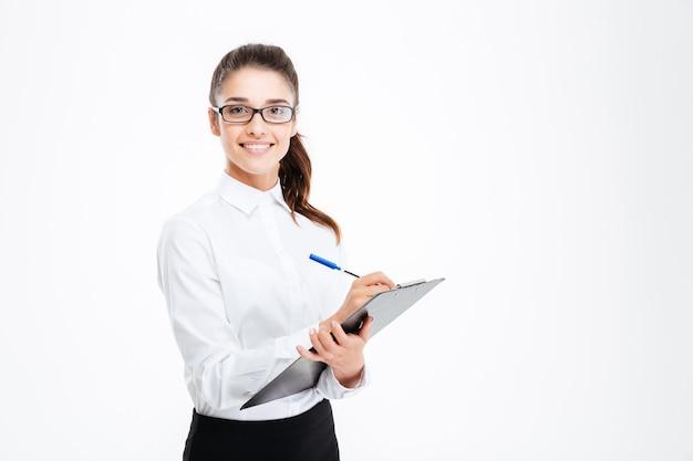 Приветливая молодая улыбающаяся деловая женщина с буфером обмена и ручкой над белой стеной