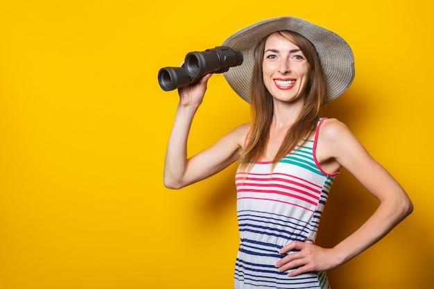 Дружелюбная молодая улыбающаяся женщина в полосатом платье держит бинокль на желтом пространстве