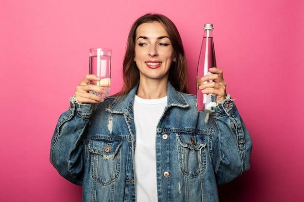 コップ1杯の水と水のボトルを保持しているフレンドリーな若い女性