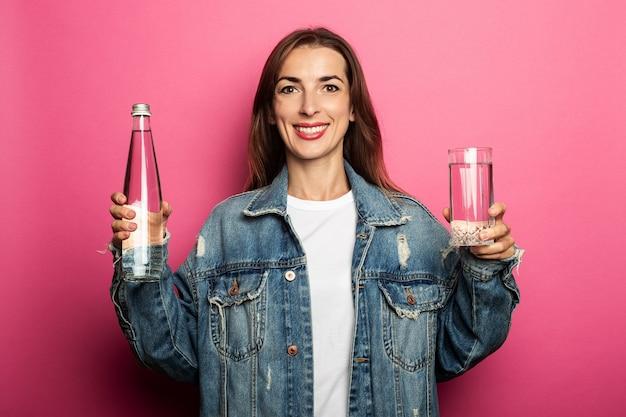 水のボトルと水のガラスを保持しているフレンドリーな若い女性