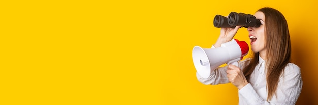 Friendly young woman holds a megaphone in her hands and looks through binoculars on a yellow background