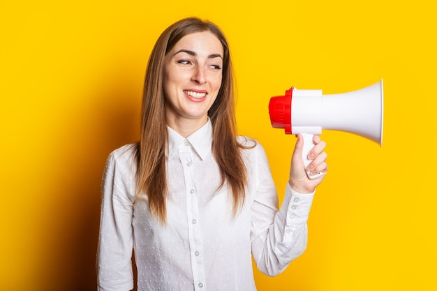 Friendly young woman holds a megaphone in her hands on a yellow background