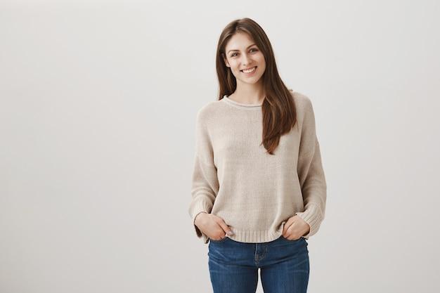 Приветливая молодая женщина выглядит веселой, счастливой на сером
