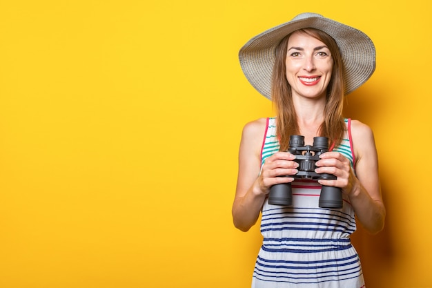 Friendly young woman smiling with a hat and a striped dress holding binoculars on a yellow space.