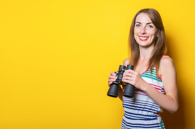 Friendly young woman in a striped dress holds binoculars on a yellow space.
