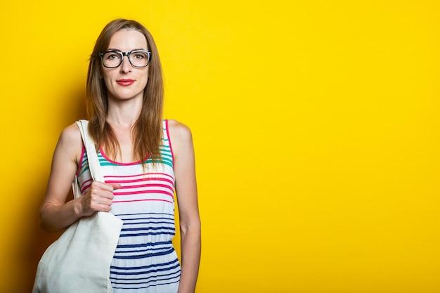 안경을 착용하는 친절 한 젊은 여자는 노란색 배경에 그녀의 어깨에 리넨 가방을 보유하고 있습니다.