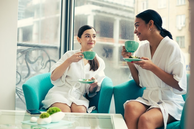 Friendly young women enjoying pleasant conversation and smiling while sitting in the bathrobes and drinking tea