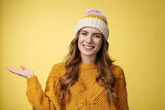 冬の帽子のセーターを着ているフレンドリーな見た目の自信を持って快適で魅力的な若いヨーロッパの女性が拡張します...
