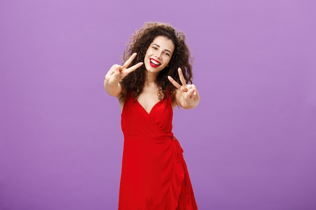 Friendlylooking peaceful european female with curly haircut in elegant red dress showing peace or vi...