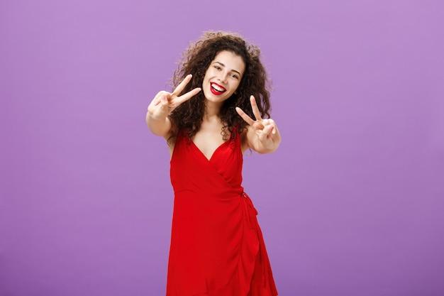 Приветливая мирная европейка с кудрявой стрижкой в элегантном красном платье демонстрирует мир и ...
