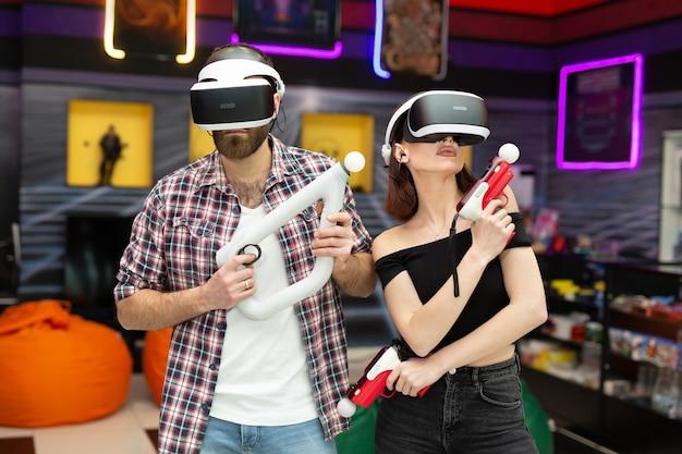友人、男性、女性は、プレイエリアでメガネとハンドモーションコントローラーと武器を備えたバーチャルリアリティヘッドセットを使用しています。