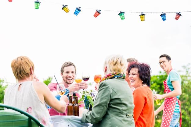 음료와 함께 토스트 파티를 축하하는 긴 테이블에 친구와 이웃