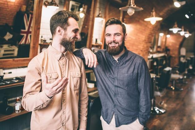 Друзья стоят вместе и смеются. парень в розовой рубашке смотрит на своего друга, который опирается на плечо.