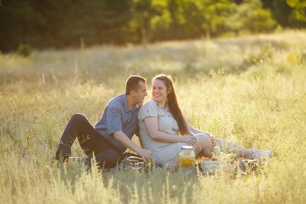 Друзья на пикнике. влюбленная пара, сидя на одеяле, пить сок и читать книгу на открытом воздухе. здоровый образ жизни. семейный отдых