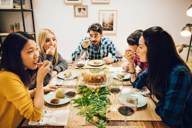 Друзья за столом едят торт