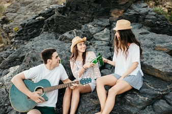 Friends at the beach with guitar and beer