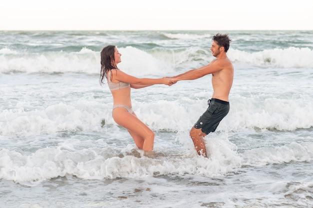 Друзья в отпуске. счастливая молодая пара весело в воде.