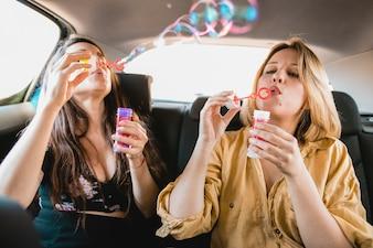 Friends blowing bubbles in car