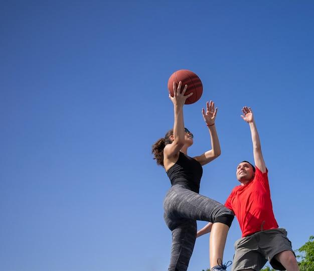 Друзья мальчик и девочка веселятся и играют в баскетбол