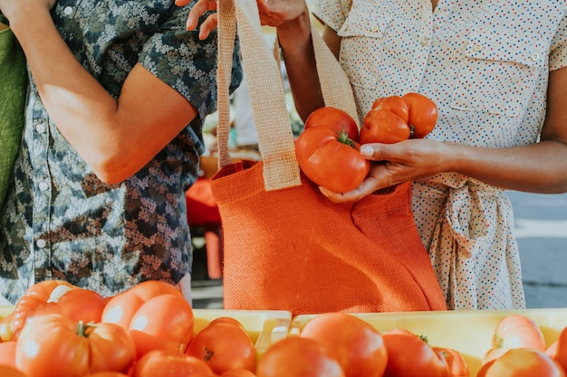 Friends buying fresh tomatoes at a farmers market
