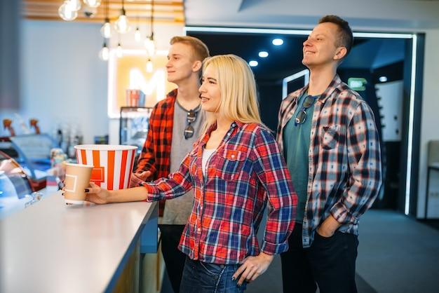 Друзья покупают попкорн в кинобаре перед просмотром. мужская и женская молодежь в зале кинотеатра