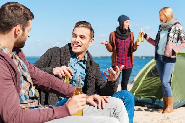 Кемпинг друзей. группа молодых веселых людей пьет пиво и разговаривает во время кемпинга на берегу реки