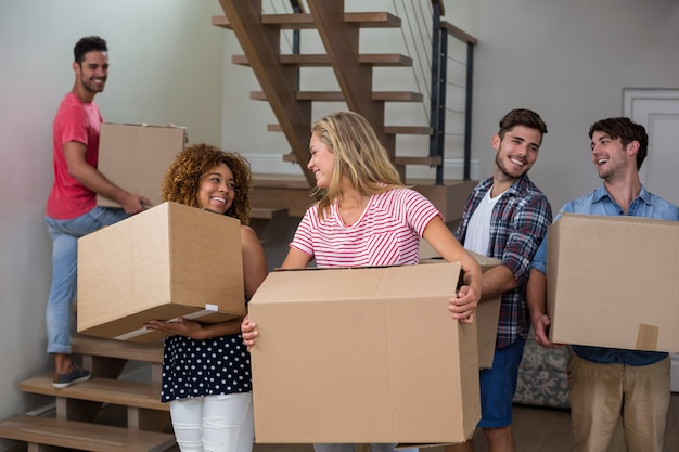 Friends carrying cardboard boxes in new house