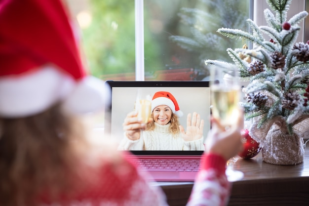 Friends celebrating christmas holiday online by video chat in quarantine. lockdown stay home concept. xmas party during pandemic coronavirus covid 19