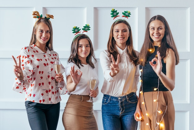 Friends celebrating christmas or new year eve party showing gestures 2020.