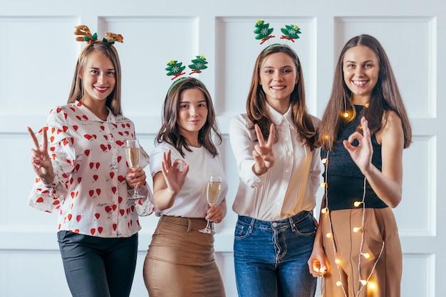 2020年のジェスチャーを示すクリスマスまたは大晦日のパーティーを祝う友人。