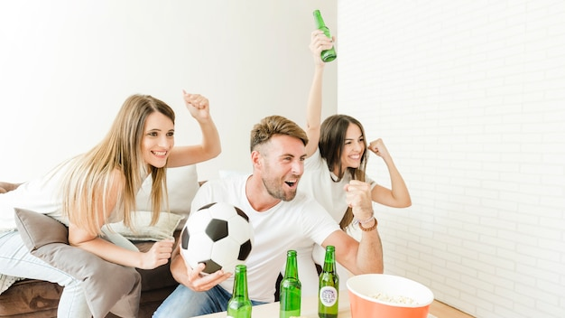 Friends celebrating goal sitting at couch