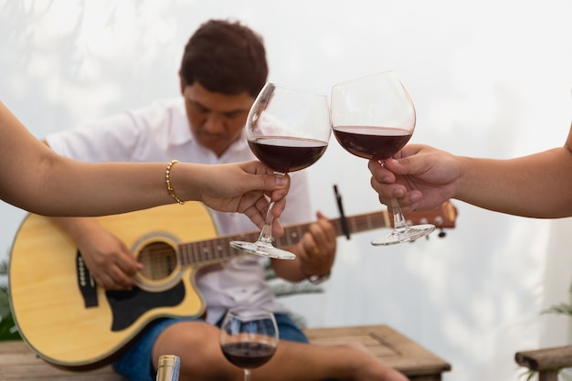 Friends celebrating and playing guitar while drinking red wine.