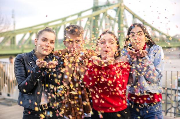 Friends celebrating on a terrace, blowing confetti