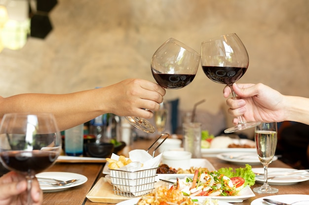 Friends celebration lunch with hands toasting glass red wine with food.