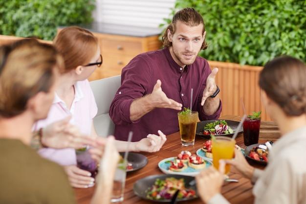 昼食時にカフェでおしゃべりする友達