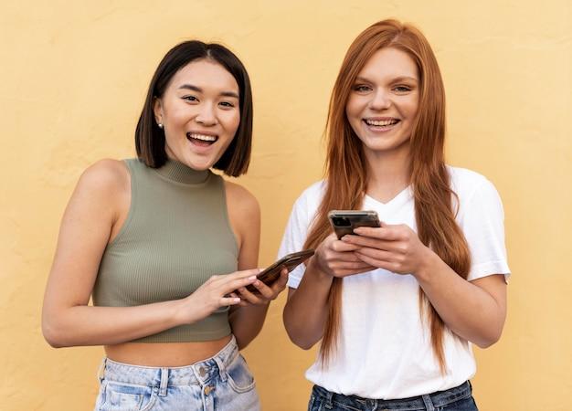 Amici che controllano i loro telefoni all'aperto