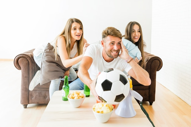 Friends cheering for football team at home