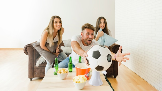 Friends cheering watching football at home