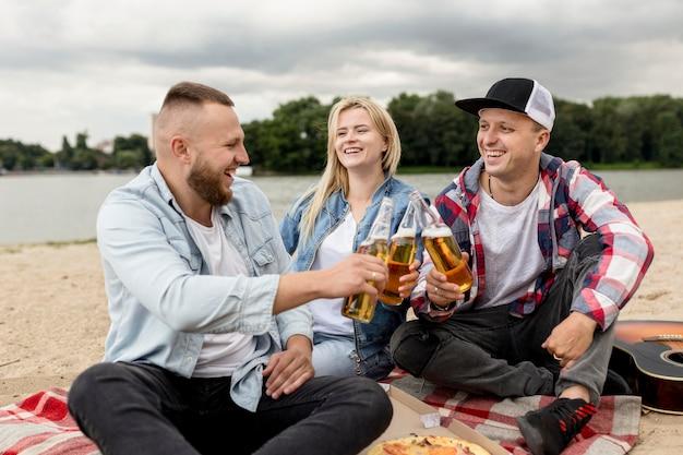 Amici in festa con bottiglie di birra su una spiaggia