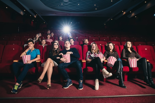 Friends in a cinema theater at an interesting movie session