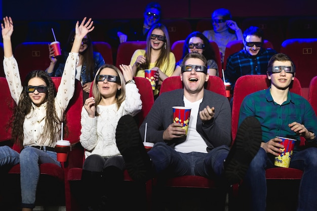 Friends at the cinema watch a funny movie with 3d glasses