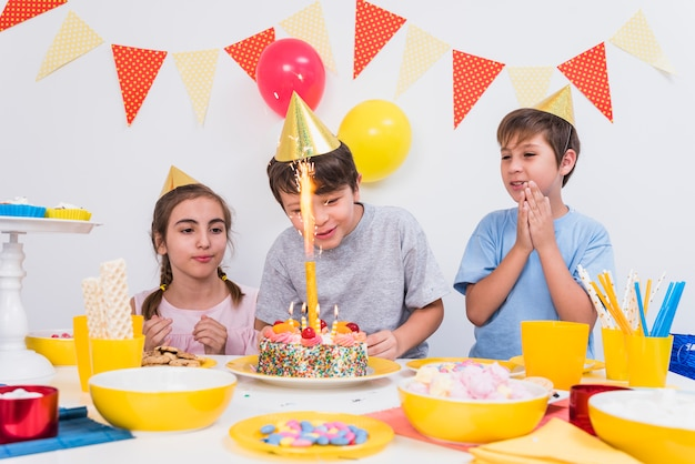 Friends clapping while boy cutting his birthday cake at home
